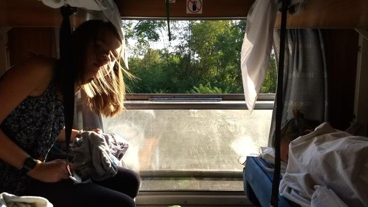 train travel around the world, a girl watches out the window on a night train across bulgaria